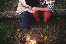 a couple sitting on a log next to a campfire