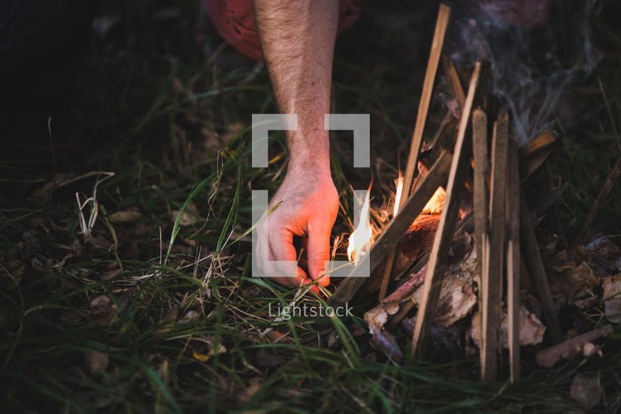 man lighting a campfire