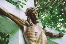 A bronze sculpture of Jesus on the cross made out of bronze hanging on a marble cross. Jesus is shown with a wound where a roman solider pierced his side with a spear.