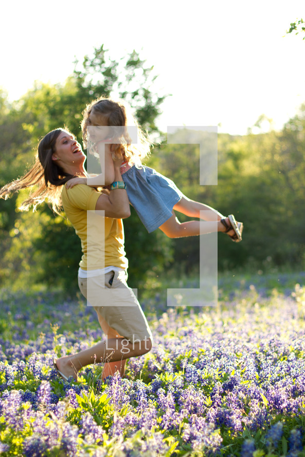 mother holding and swinging her child in a field of blue bonnets