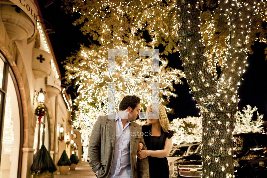 Happy couple walking down lighted sidewalk street