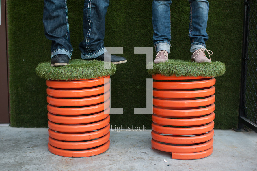 man and woman standing on turf grass covered stools