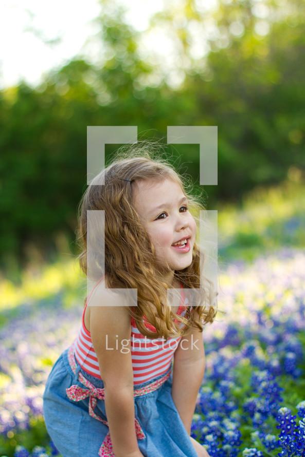 girl child in a field of Blue bonnets