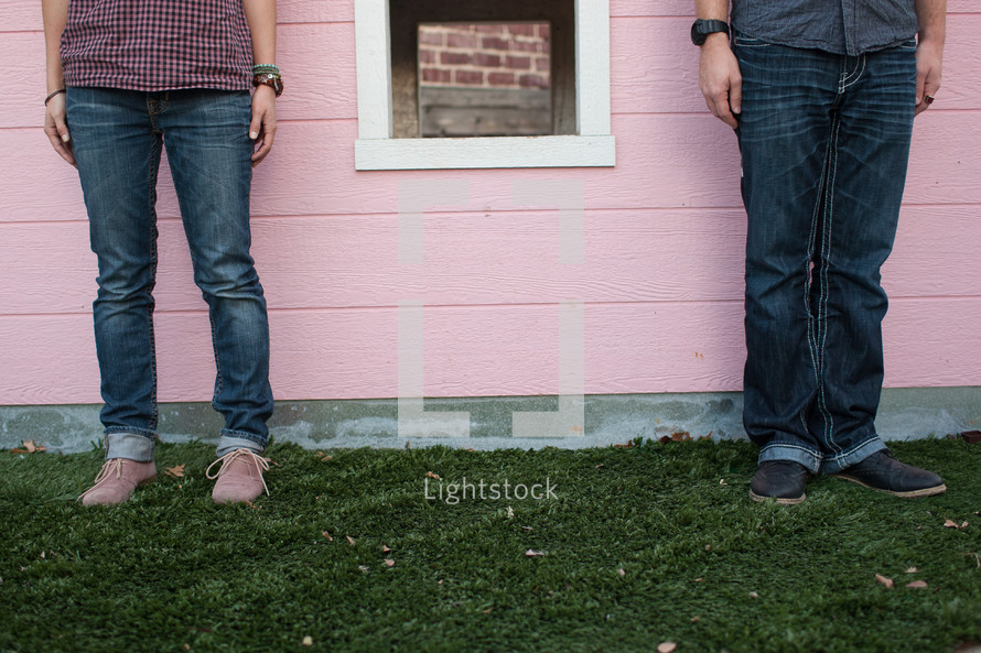 Man and woman standing in grass beside window on pink house.