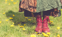 A woman in red boots standing in a field of flowers.