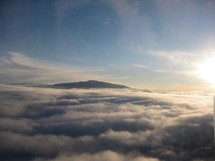 mountain peak peaking above the clouds