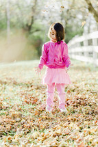 a young girl playing in fall leaves