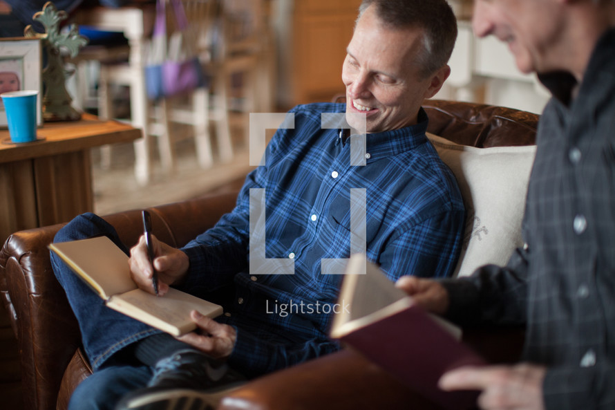a man writing in a journal at a Bible study