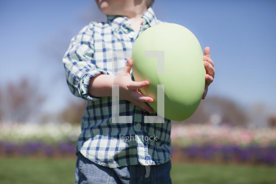 Boy holding a giant Easter egg.