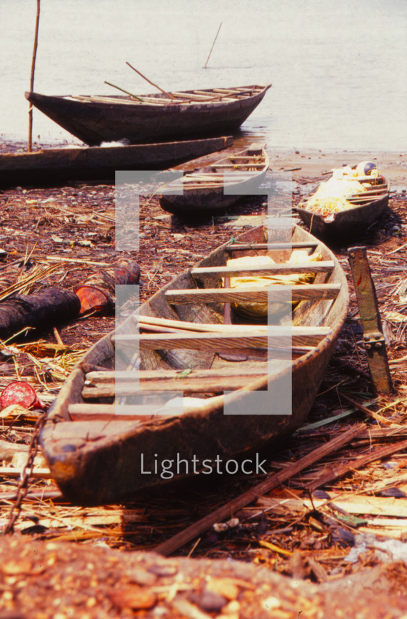 Wooden row boats on the shore of a lake.