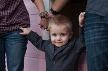 Toddler boy in suit hanging on the jean pockets of man and woman standing by pink house.