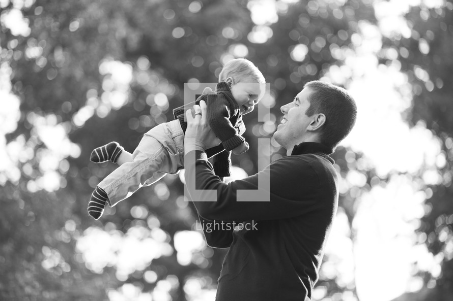 father holding a boy baby in the air
