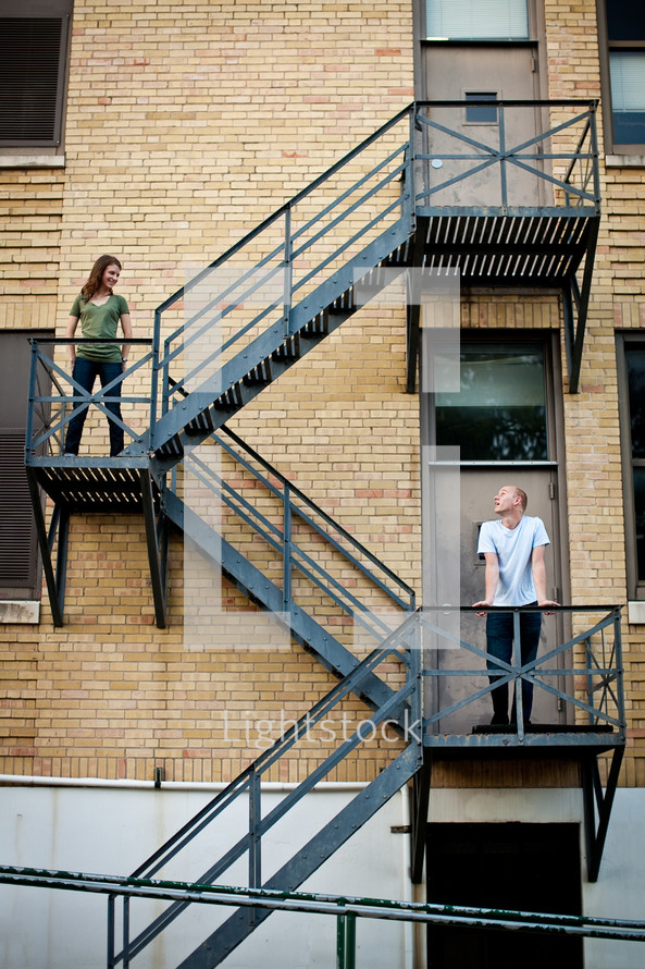 A couple stands on different flats on a stairwell