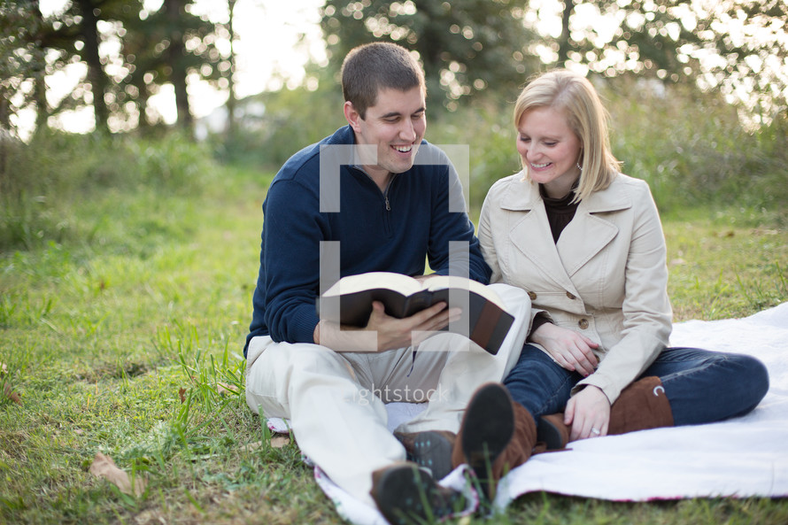 A couple reading the bible together outside