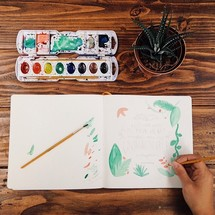 Painting with watercolors at a wooden table.