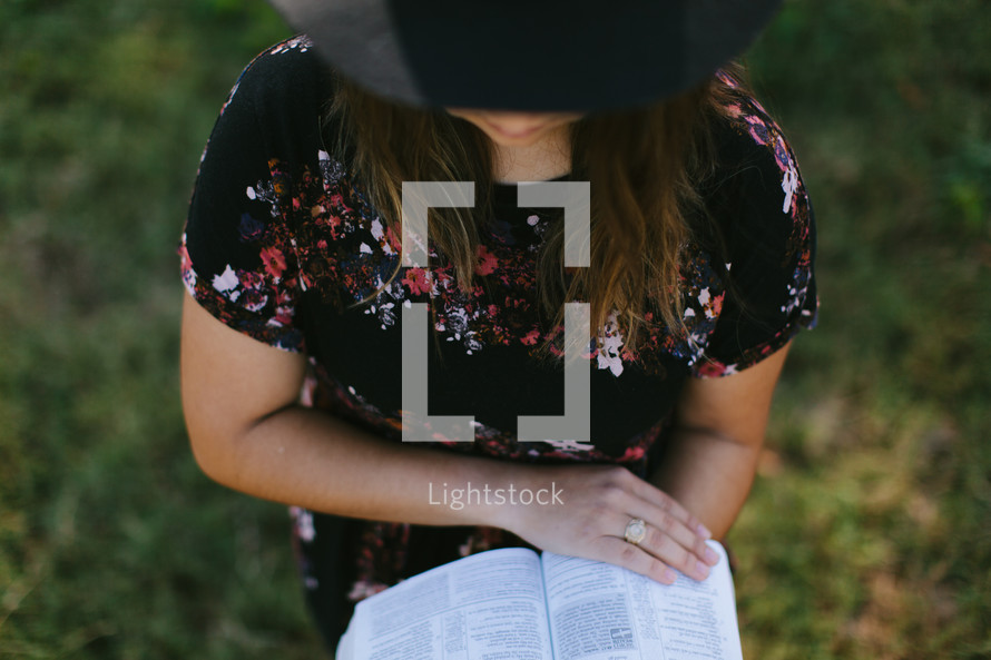 a woman in a hat reading a Bible