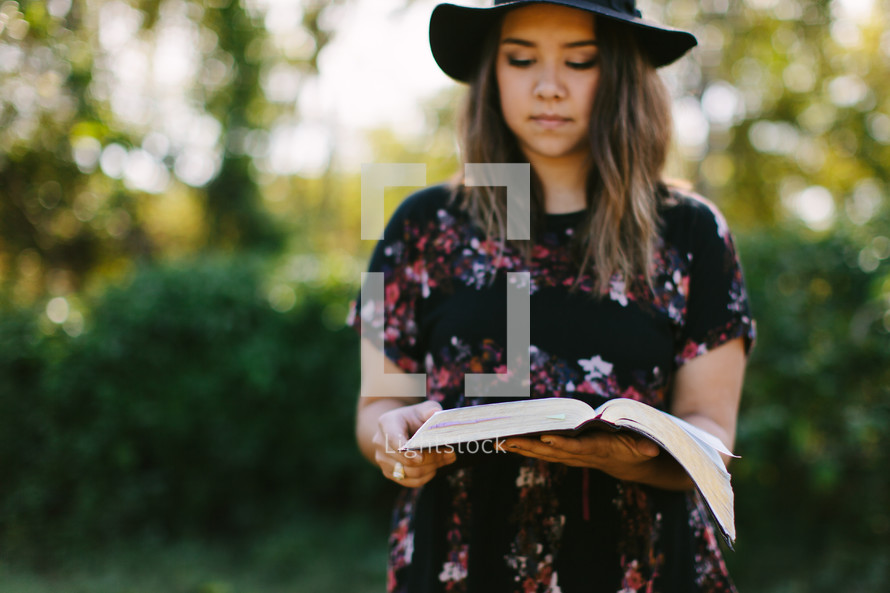 portrait of a young woman standing outdoors reading a Bible