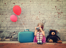 a little girl sitting with balloons and luggage