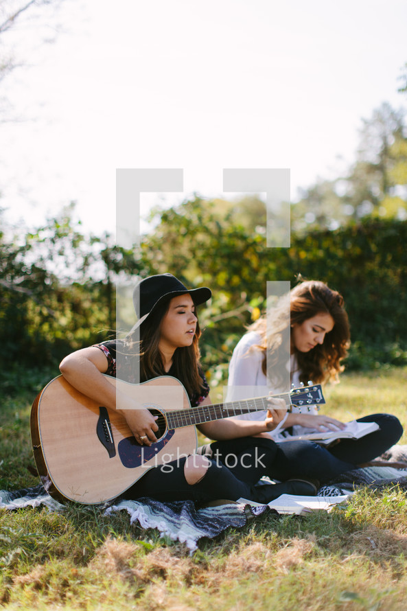 teen girl playing guitars and singing outdoors