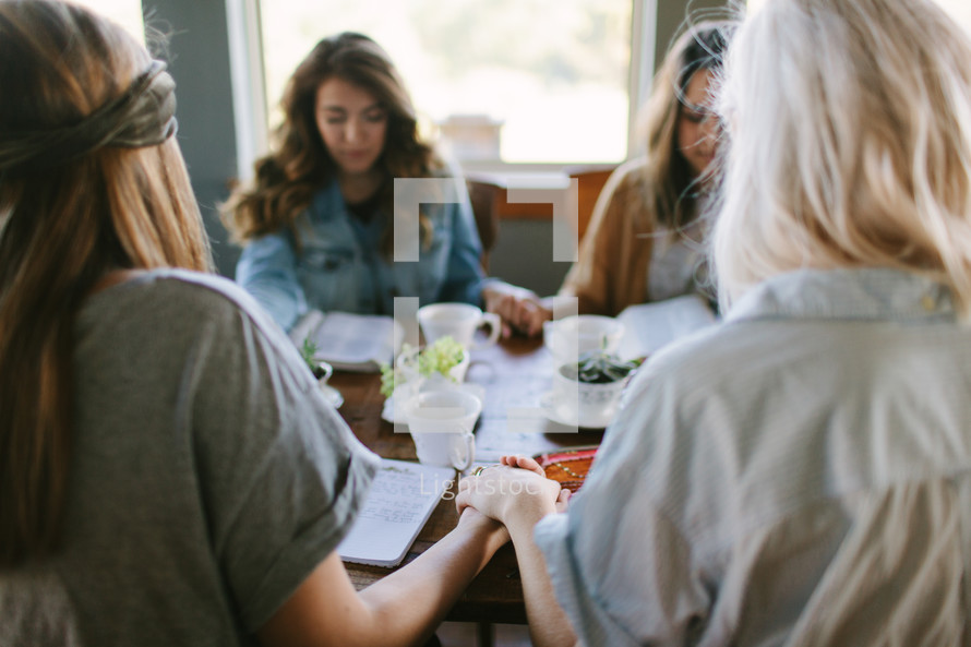 young women at a Bible study holding hands in prayer