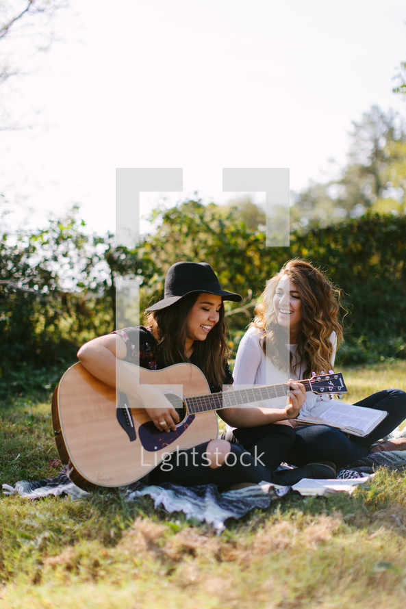 playing guitar, reading, blanket, Bible, young woman, girl, woman, sitting, outdoors
