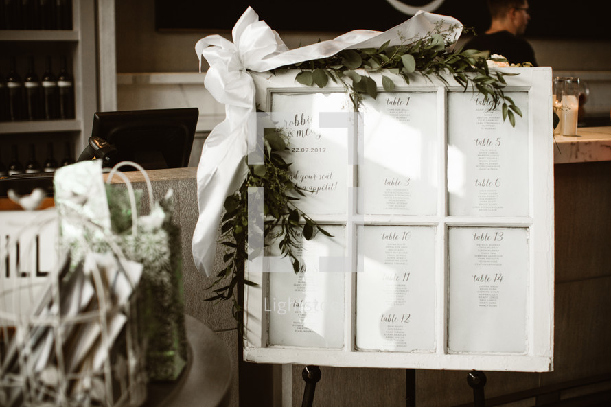 old window pane with numbered table seating assignments