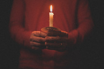 A man wearing a red shirt holding a candle