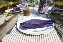 purple napkins on plates for a dinner party