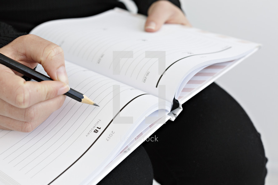 a woman whiting in a planner