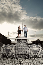 couple holding hands while standing on a tank