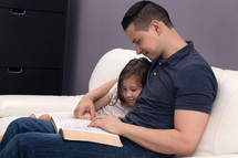Man Reading Holy Bible to his daughter