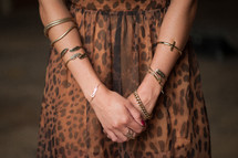 Woman's arms with gold bracelets.