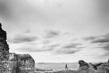 man walking on remaining walls at a ruins site