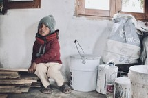 a child in a room surrounded by construction materials