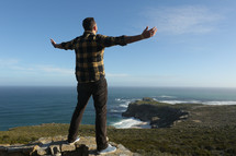 Man on mountain cliff with open arms