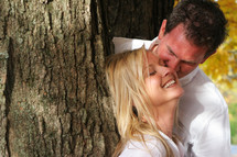Couple leaning on a tree smiling