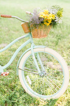 A basket of flowers on a bicycle.