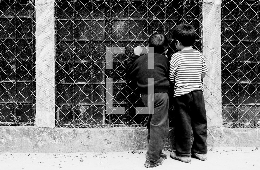 Boys looking inside window with bars