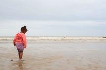 toddler girl walking on a beach