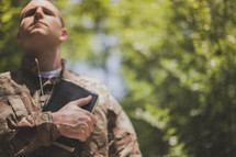 serviceman holding a Bible over his heart in prayer