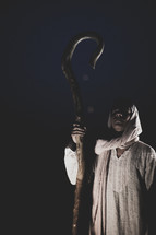 face of a shepherd with his staff standing in darkness