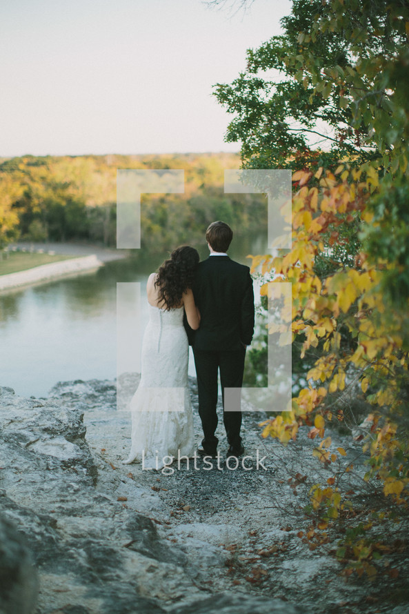 bride and groom looking out at a lake