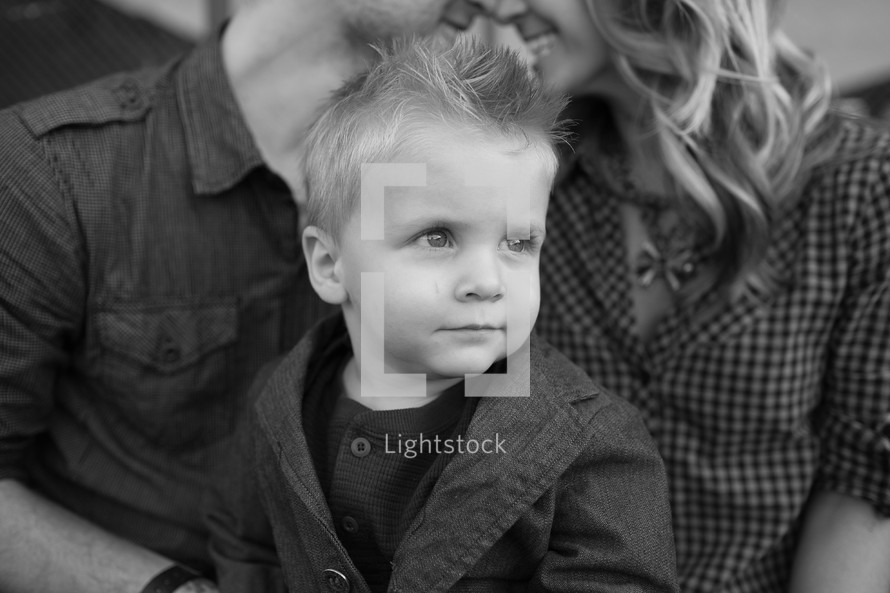 toddler boy sitting on mother and father's lap