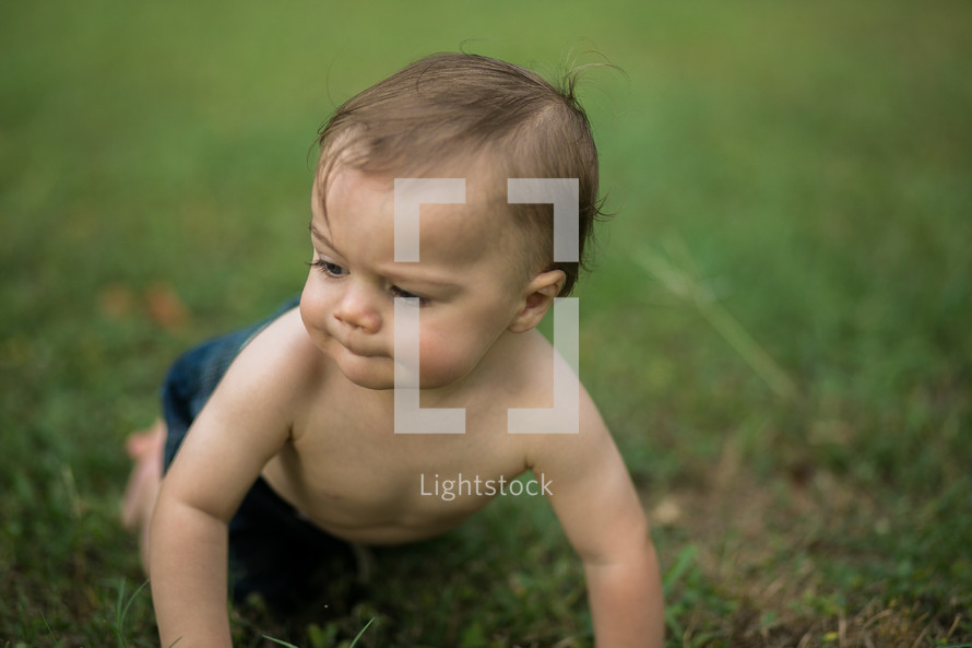 A baby crawling on grass