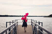 a woman walking carrying helium balloons on a dock