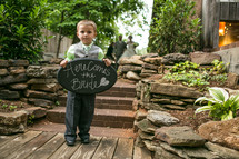 ring bearer holding a sign