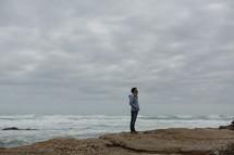 Man standing on cliff overlooking ocean
