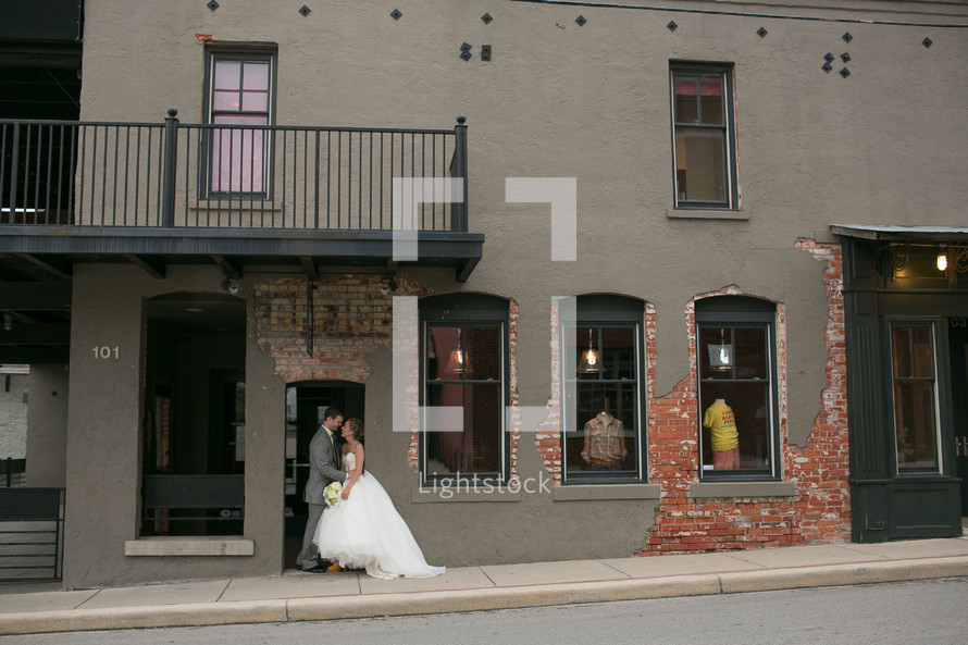 bride and groom kissing in front of a store