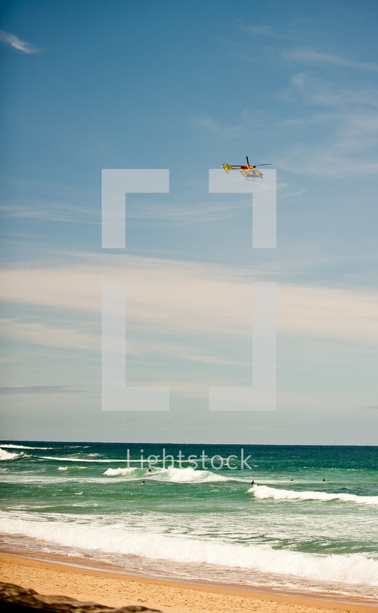 coast guard helicopter flying over a beach