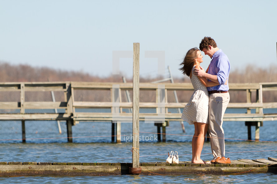 A couple hugging on a dock